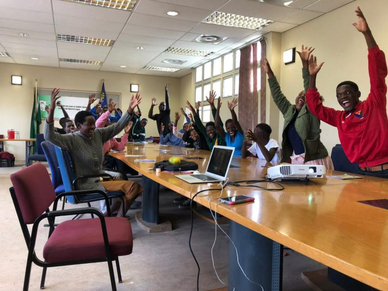 a group of deaf youth seated around a table with their hands waving in the air