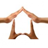 Photo shows four hands, arranged together into the shape of a house.