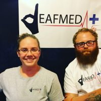 A woman and a man are looking at the camera. On the wall behind them is a sign that has a logo for DeafMed. The