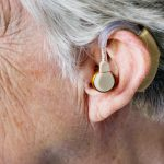 Photo shows an old person wearing a hearing aid. The photo centers the ear without showing the person's face.