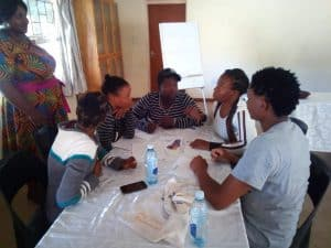 a group of deaf youth are sitting around a table discussing