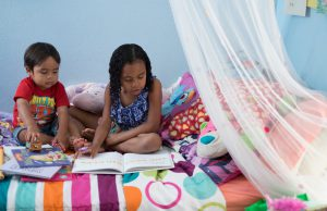 Two children are seated together on a bed. One is reading, the other is playing with a toy truck while looking at a book.