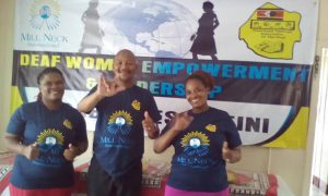 two women and a man stand in front of Deaf Women Empowerment Leadership banner smiing and signing ILY